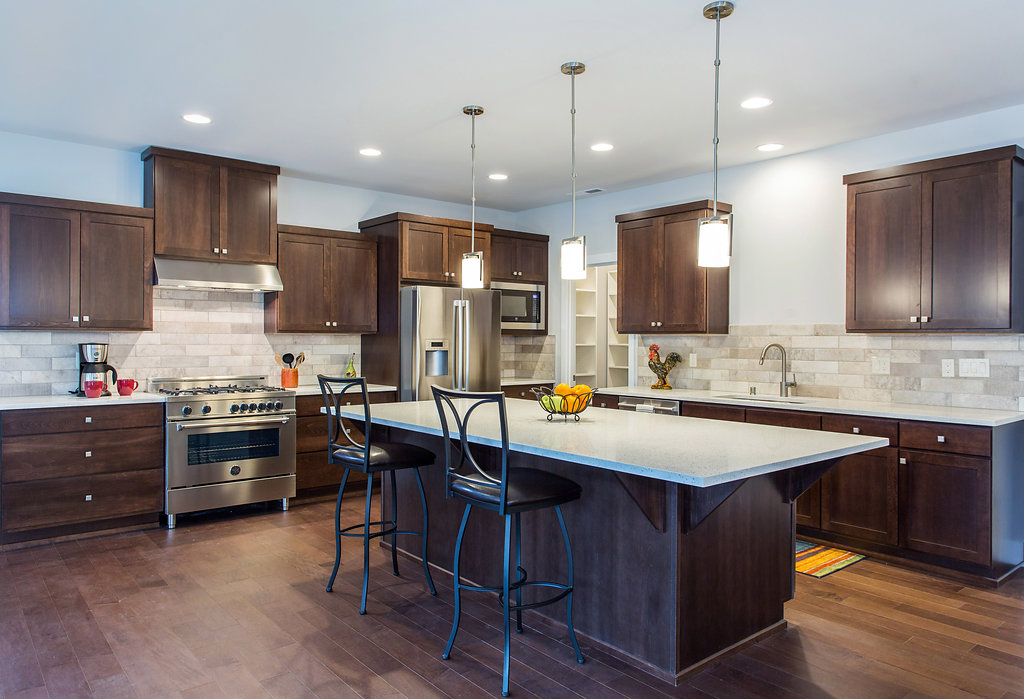 Kitchen with kitchen island, gas range, quartz counters, pendant lighting, custom cabinets.